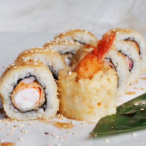 roll with shrimp tempura on a wooden table green leaf