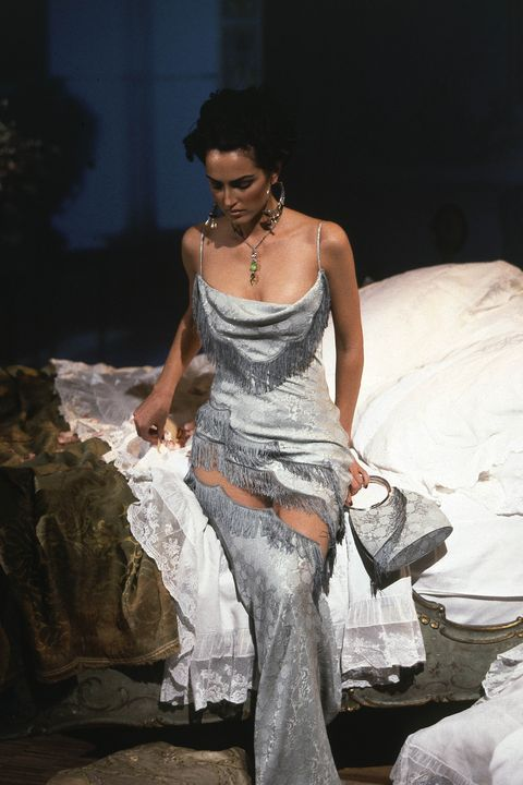 model on the runway for the boudoir inspired springsummer 1998 christian dior ready to wear collection designed by john galliano, wearing a blue fringed brocade sheath dress with draped bodice, matching purse, jewelled pendant necklace, and oversized hoop earrings photo by guy marineaucondé nast via getty images