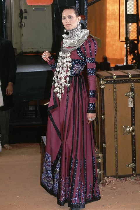 model on the runway for the fallwinter 1998 christian dior orient express couture collection designed by john galliano, wearing a purple full length dress with puffed sleeves trimmed with black ribbons and blue floral embroidery and silver ruff like necklace with hanging oversized strands of beads photo by guy marineaucondé nast via getty images