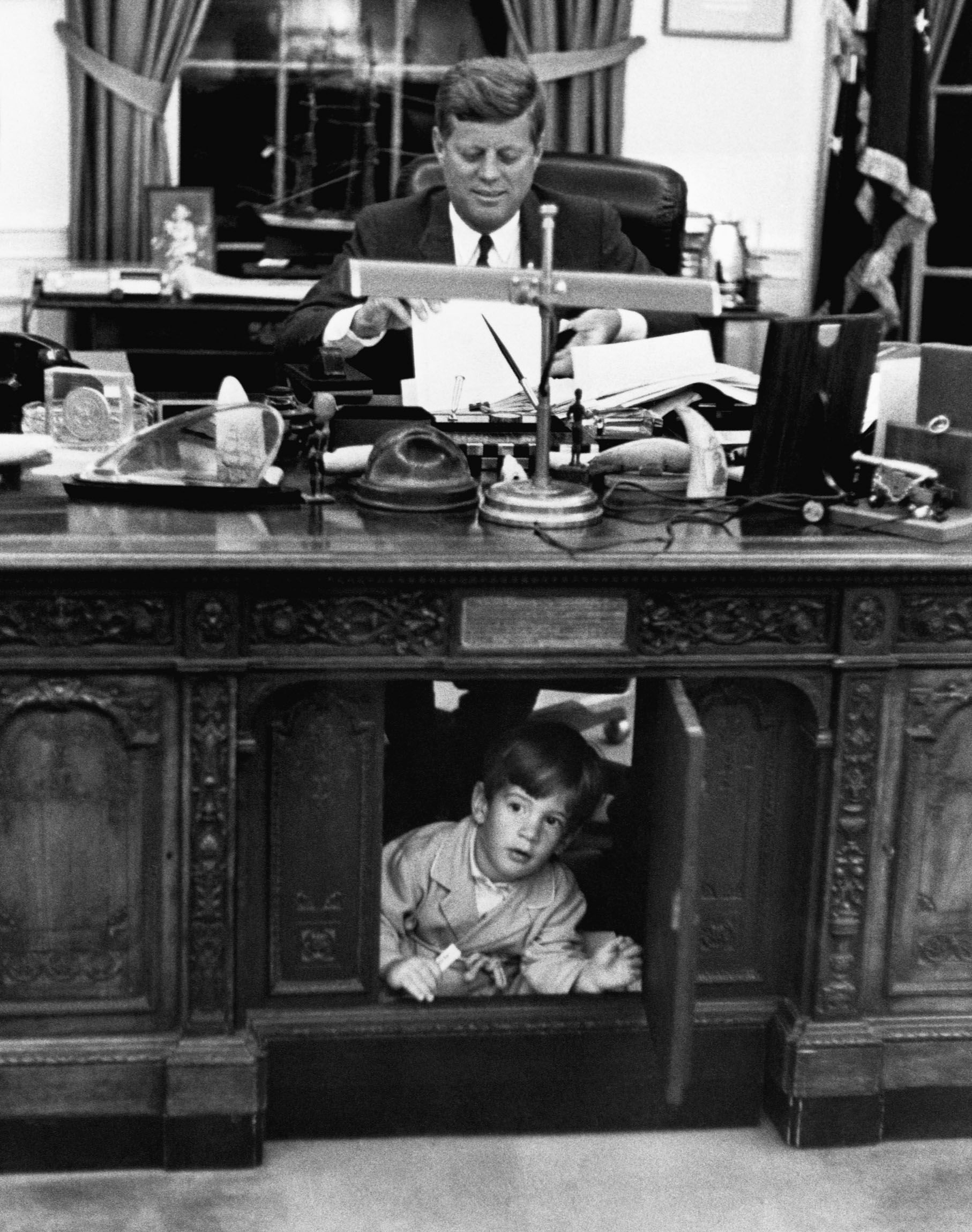 John F. Kennedy Jr. exploring his father's desk in 1962.
