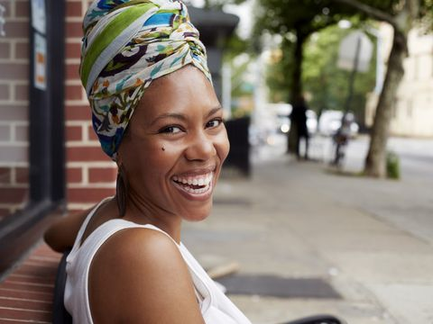 Black woman smiling on bench on city street