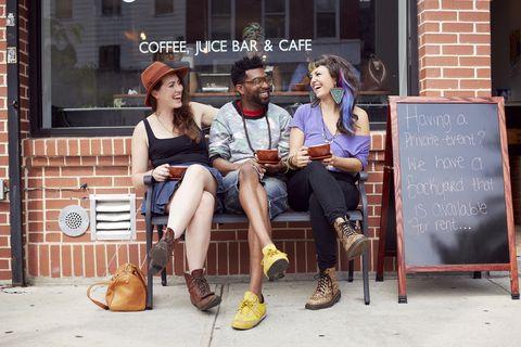 Friends sitting outside coffee shop on city street