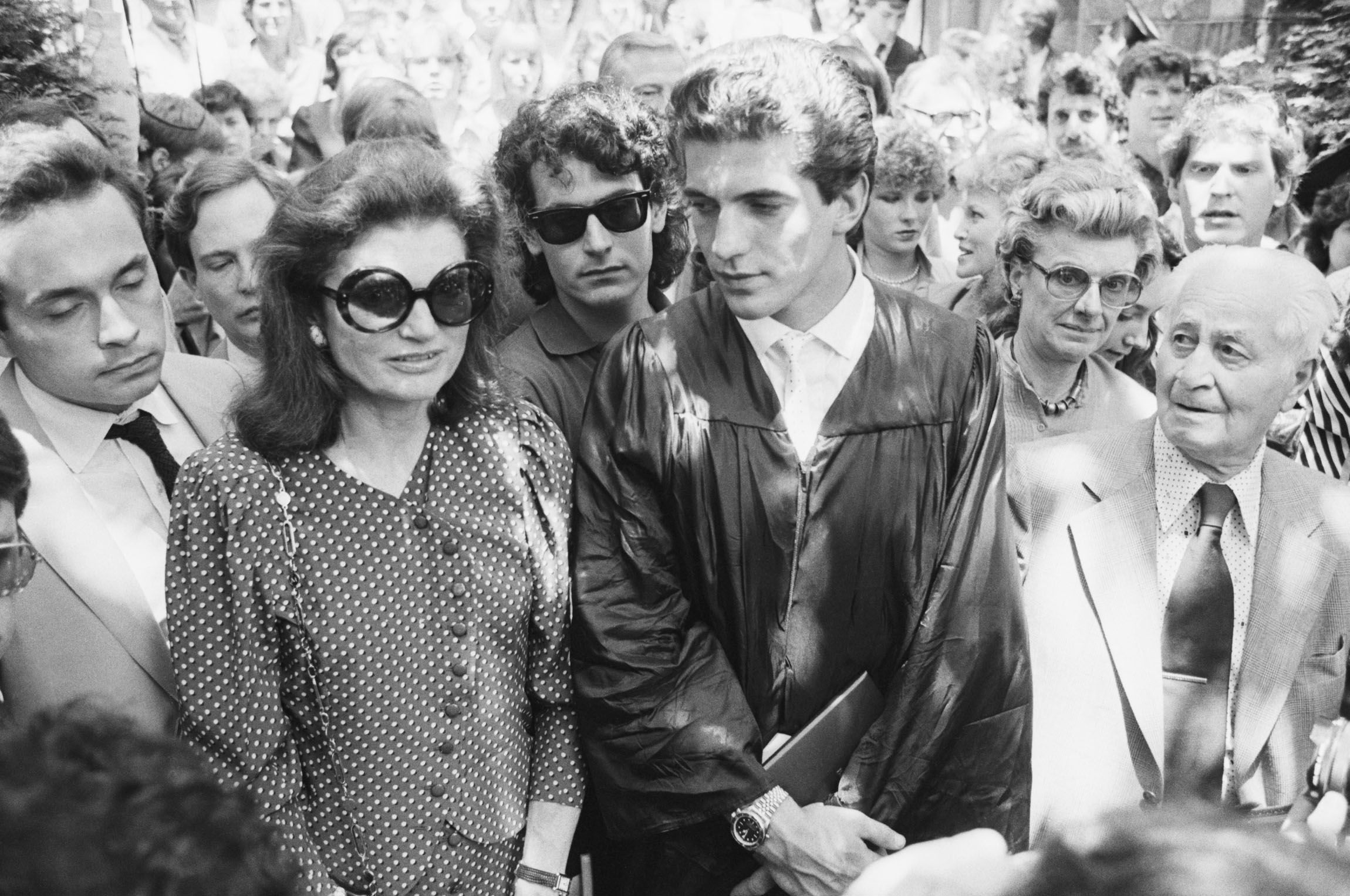 John F. Kennedy Jr. looks at his mother Jacqueline Kennedy Onassis as they stand at his graduation ceremony at Brown University, where John received a Bachelors of Arts in History on June 6, 1983.