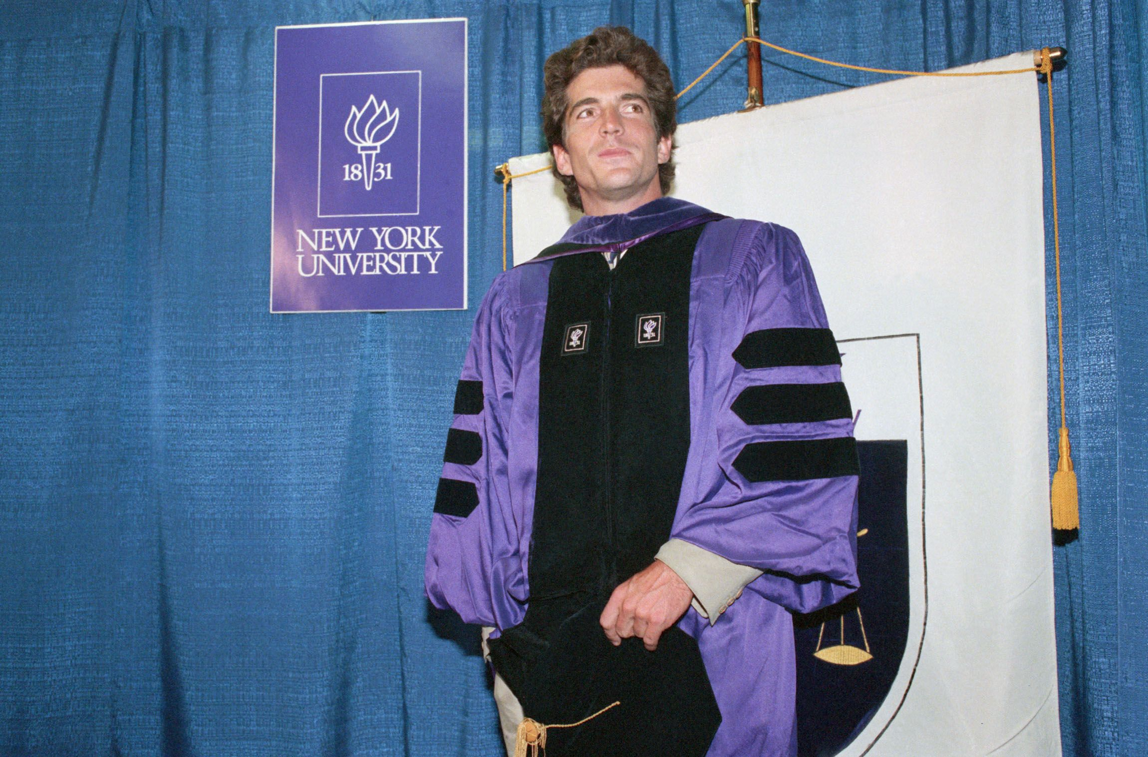 Twenty-eight-year-old John F. Kennedy Jr. poses in his gown at graduation exercises for the New York University Law School on May 19, 1989.