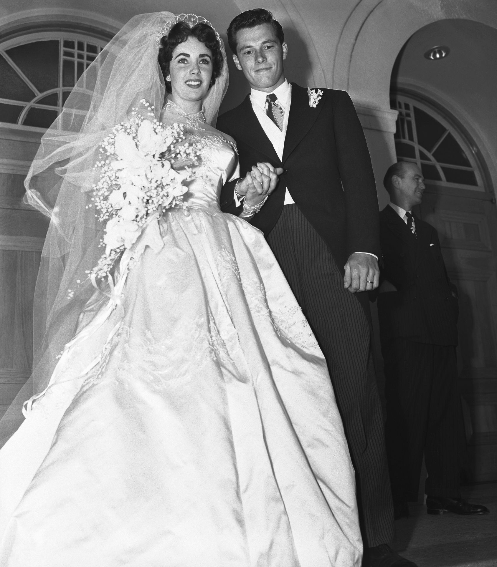 Elizabeth Taylor's First Wedding Dress American hotelier Conrad Hilton's son Nicky Hilton married Elizabeth Taylor when she was just 18 in a ceremony in Beverly Hills. MGM organized the fabulous event, and Elizabeth's dress was designed by famed costume maker Helen Rose.