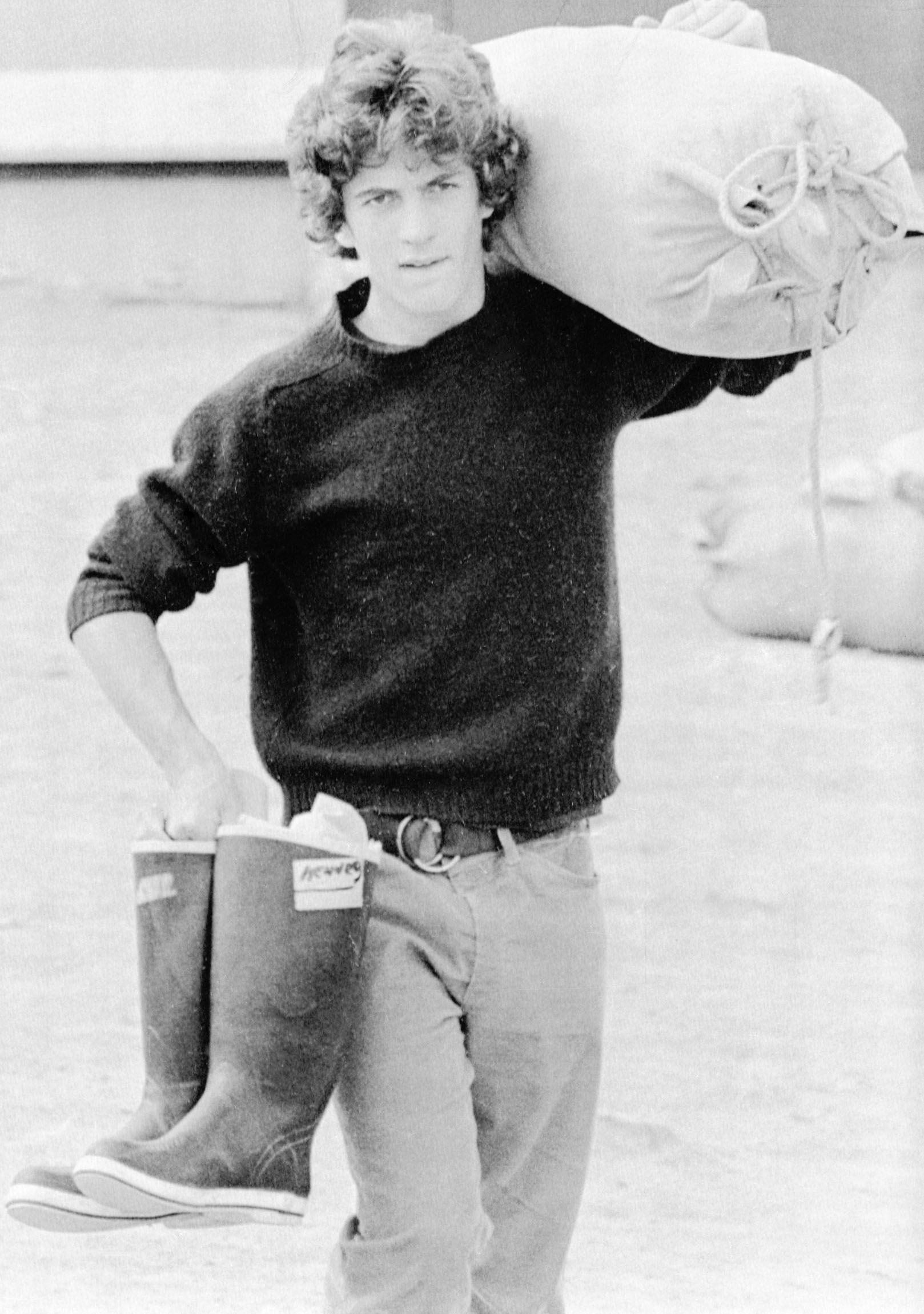 John F. Kennedy Jr. carries seabag and boots as he heads down to the dock in Rockland, Maine on July 12, 1977.