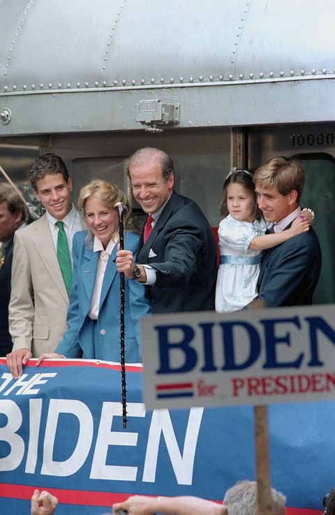 original caption wilmington, delaware sen joseph biden of delaware smiles as he grabs a walking stick presented him for the campaign by a supporter as he leaves aboard a train for washington after announcing for president here 69 looking on are wife, jill, daughter ashley and sons beau and hunt