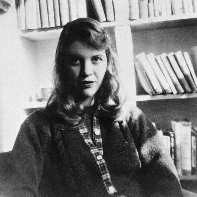 original caption photo shows author sylvia plath seated in front of a bookshelf