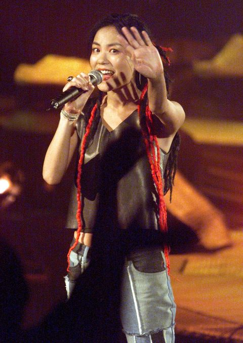 kuala lumpur, malaysia  hong kong pop star faye wong waves to fans during the first night of her two day concert in kuala lumpur 21 august 1999  tickets were sold out for the performance      electronic image  afp photojimin lai photo credit should read jimin laiafp via getty images