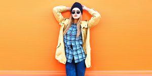 Fashion pretty woman model posing over colorful orange background