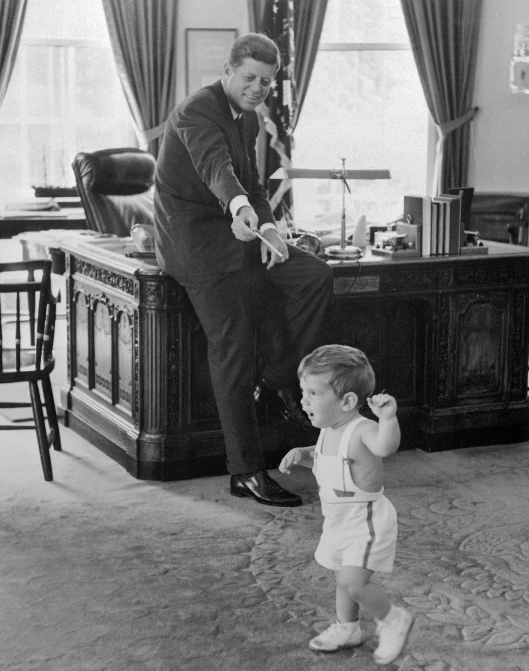 The White House released this picture showing President Kennedy watching his 18-month-old son, John Jr., playing in the Chief Executive's office in 1962.