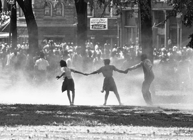 three demonstrators join hands to build strength against the force of water sprayed by riot police in birmingham, alabama, during a protest of segregation practices