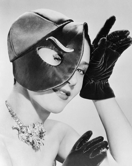 schiaparelli, in a surrealistic mood, designs this red satin, visored evening cap with an elongated peephole for the eye a diamond clip from van cleef  arpels makes a weird eyebrow