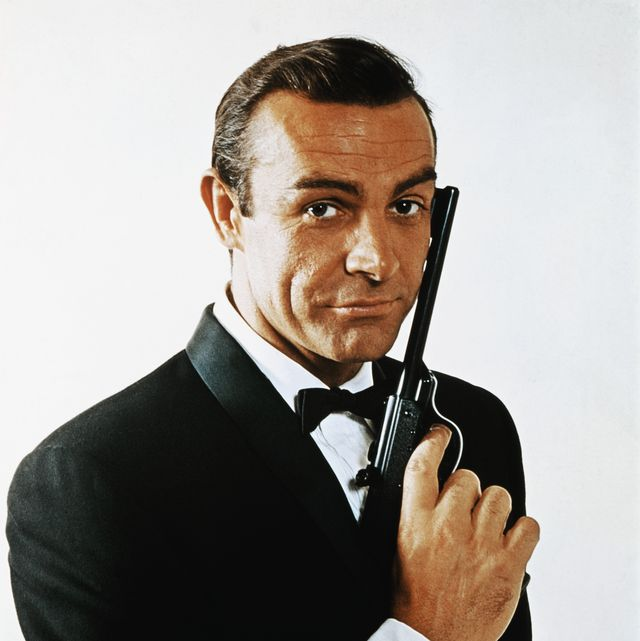 original caption waist up portrait of sean connery, as james bond, caressing the barrel of a gun against the side of his face connery is wearing a tuxedo and bow tie and smiling slightly