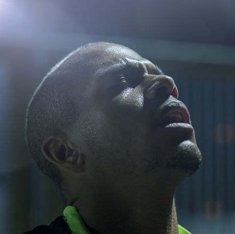 portrait of a male urban runner at night, head and shoulders only, eyes closed, looking away from camera, low key bokeh background, shot through old glass, landscape composition, backlit, one male only aged 25 to 30