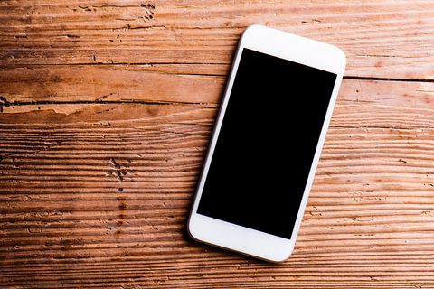 Smartphone laid on an old office desk, copy space