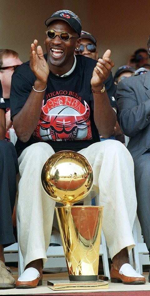 chicago, il   june 16  chicago bulls player michael jordan applauds as he sits with one of the teams six nba championship trophies he has helped the bulls win in the past eight seasons during the teams championship rally in chicago, il 16 june the bulls defeated the utah jazz four games to two in the nba finals to win their third straight nba title  photo credit should read peter pawinskiafp via getty images