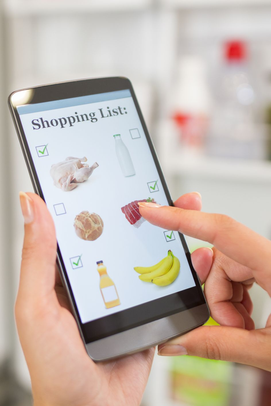 Woman making shopping list on phone connected to the refrigerator