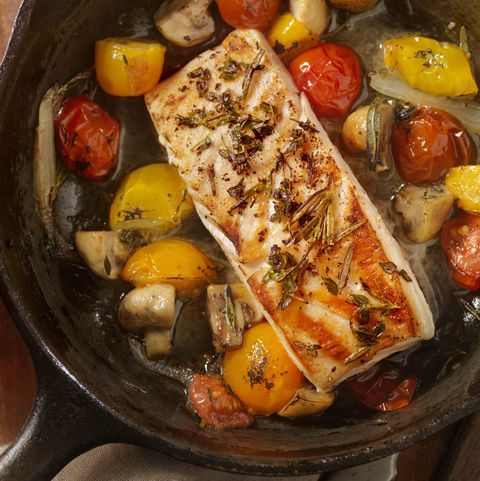 fish and tomatoes in cast iron skillet