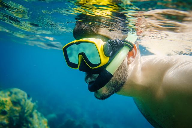 a man snorkels in the waters off anse chastanet beach in soufriere, saint lucia