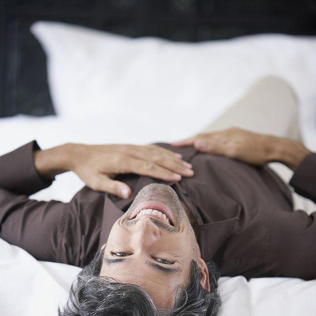 hombre tumbado en la cama para ilustrar un reportaje sobre los juguetes sexuales masculinos de diversual más vendidos en la cuarentena