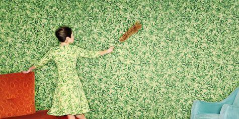 woman dusting wallpaper