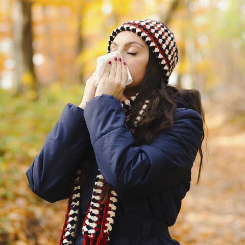 Woman sneezing in handkerchief at autumn