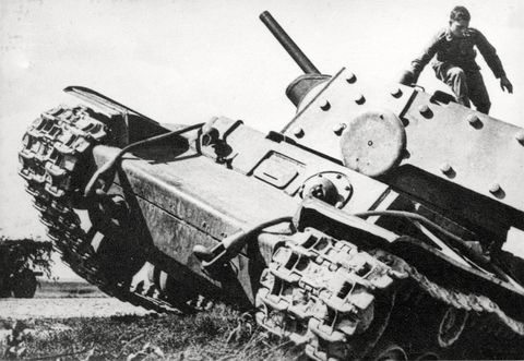 An abandoned KV-1 tank is inspected by a German soldier.