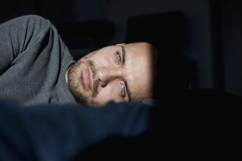 chico joven tumbado de lado sobre fondo negro mirando a la cámara