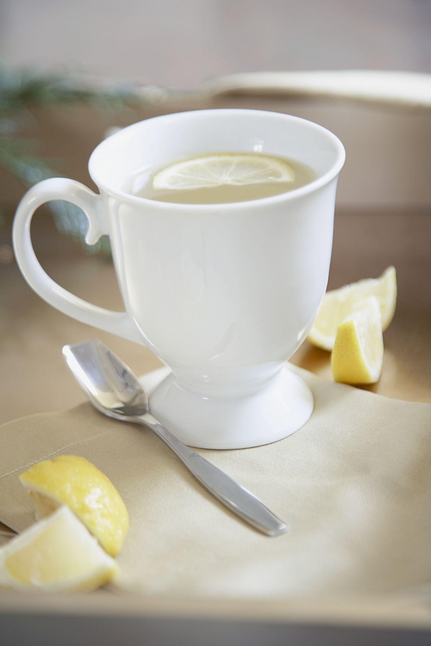 Lemon slice floating in coffee cup