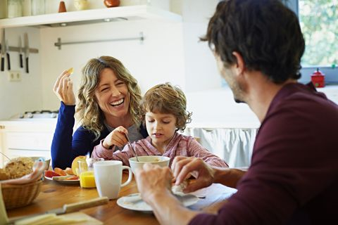 happy family of three enjoying breakfast at table in domestic kitchen
