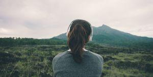 Woman in headphones listening music in nature