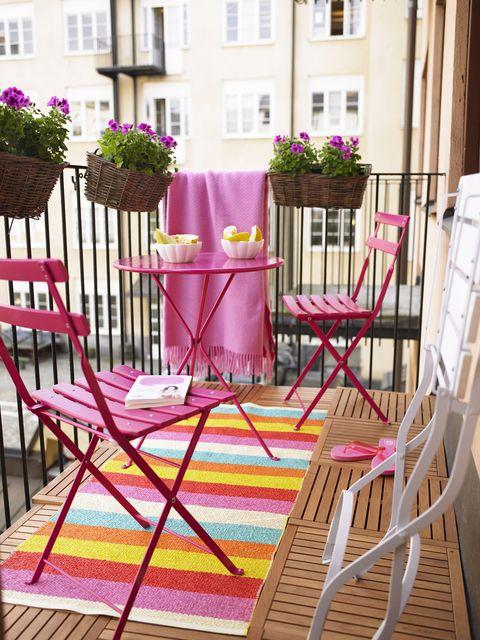 Mini comedor de mobiliario rosa en un balcón.