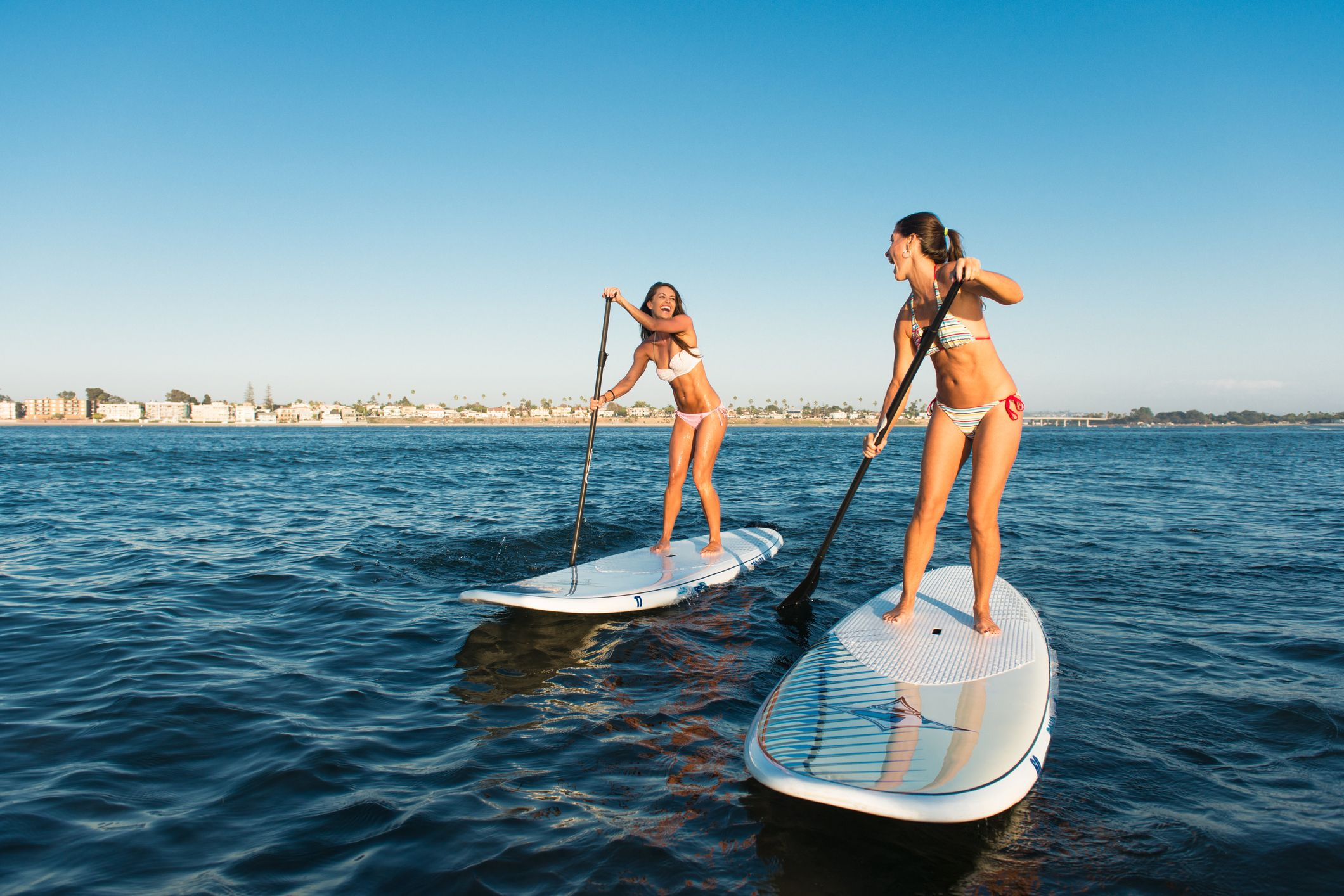 Two women chatting whilst stand up paddleboarding, Mission Bay, San Diego, California, USA