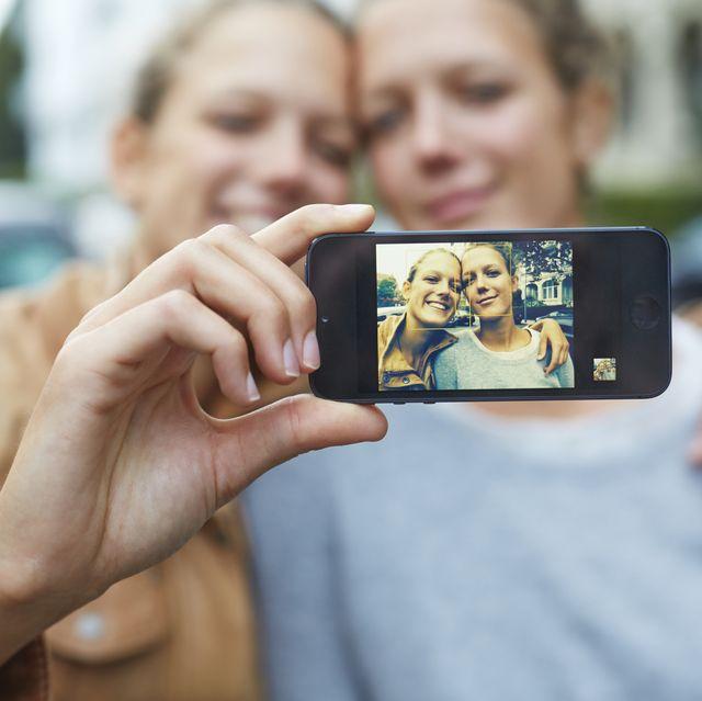 happy twin sisters taking selfie