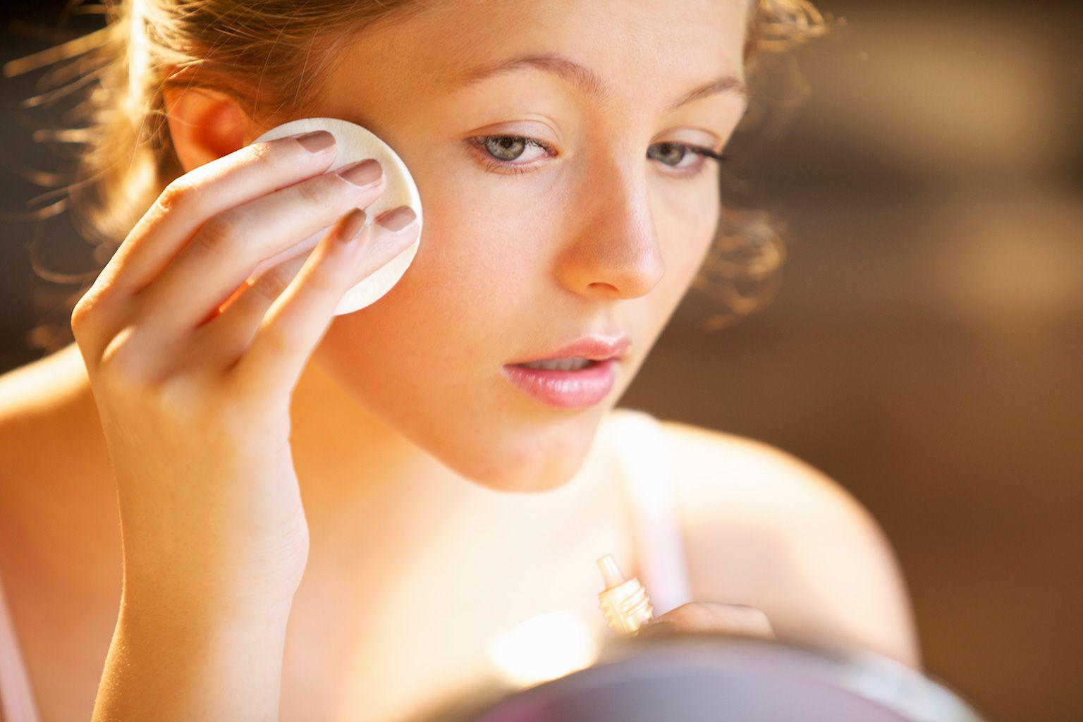 Chica joven limpiándose la piel.
