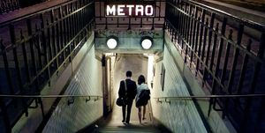 Couple of young people entering a station of the Paris Metro at night. Paris, France