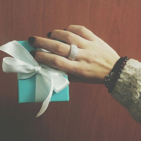 Cropped Image Of Woman Holding Wrapped Gift With White Ribbon