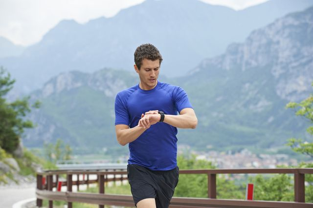 man, blue shirt, running and wachting his watch