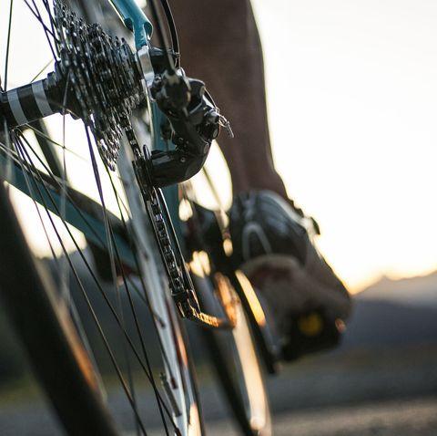 closeup of a road cyclist riding towards sunset