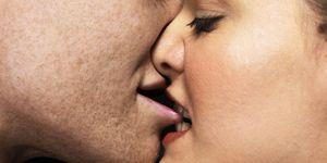 Woman biting man's lips, close up
