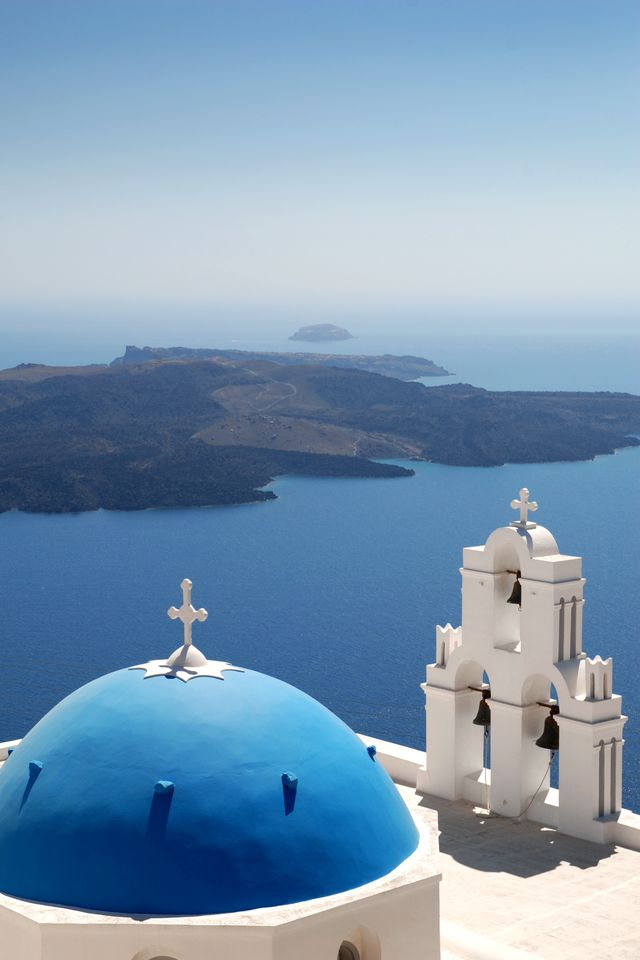the blue dome and bells of a small church in firostefani, santorini, greece the black island in the background is nea kameni, at the centre of the volcanic caldera, with the aegean sea fading into the horizon