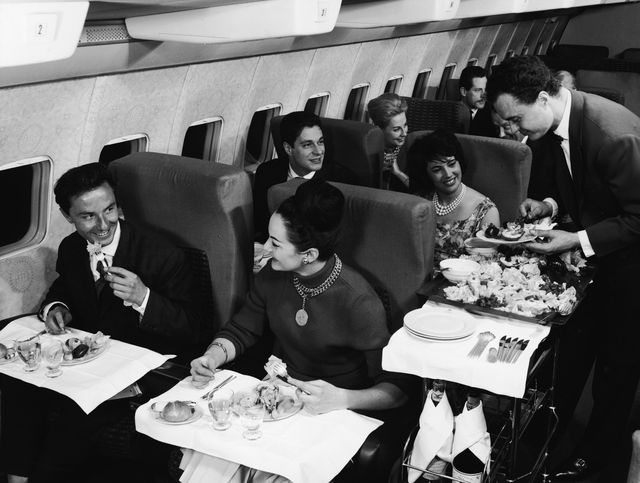 interior view of the first class compartment of a commercial passenger plane a boing shows, in the foreground, a well dressed couple as they smile and enjoy their meal, while behind them a flight attendant in a bow tie serves another happy couple, 1950s photo by authenticated newsgetty images