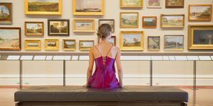 Caucasian woman in evening gown admiring art in museum