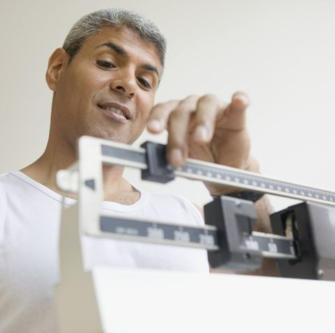Middle aged man weighing himself
