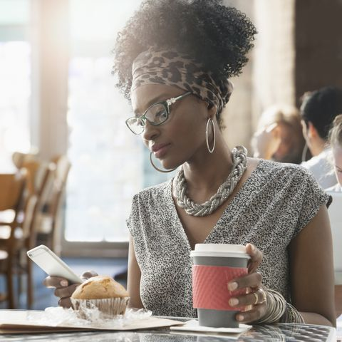 Woman using cell phone at breakfast in cafe