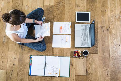 student sitting on wooden floor