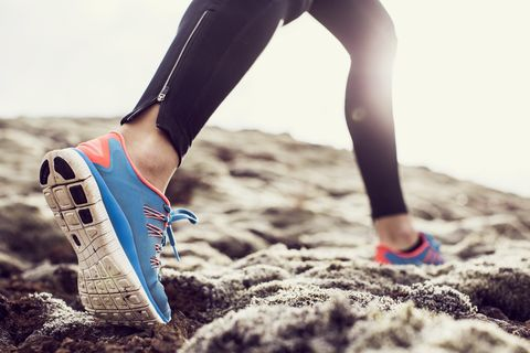 close up, low angle shot of a female runners trainers, running through mossy terrain in iceland blue trainers, black running leggings with backlit sunshine