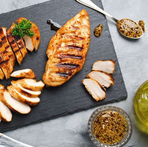 grilled chicken fillets on slate plate gray concrete background