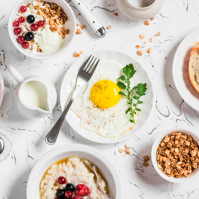 breakfast spread on marble counter with egg, greek yogurt and fruit, toast, and veggies